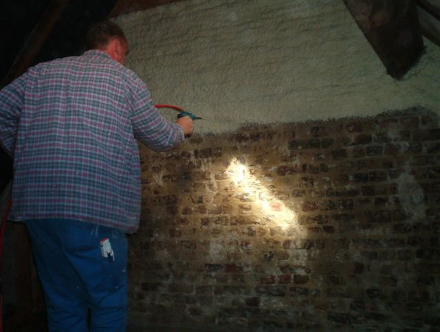 Brick wall being spray foam insulated